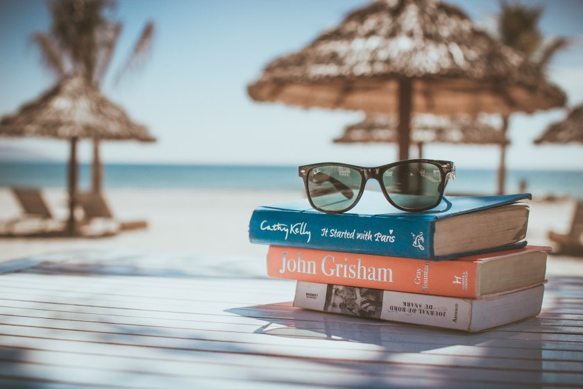 Black framed Ray-Ban Wayfarer sunglasses on top of a pile of books, with beach scene in the background
