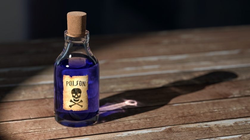 Bottle of blue liquid labelled poison sits on a wooden surface