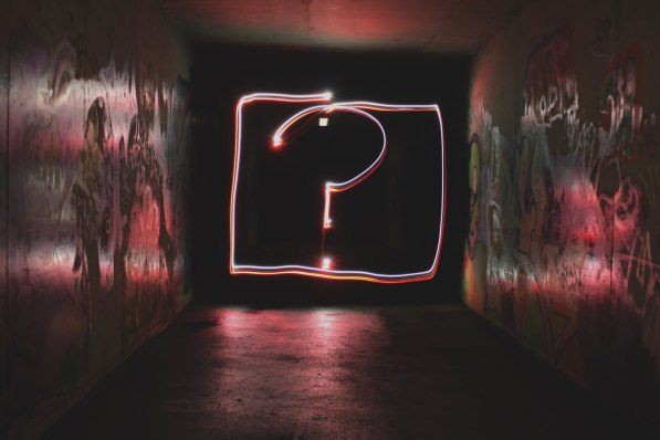 Neon lighting depicts a pink question mark at the end of a dark passage