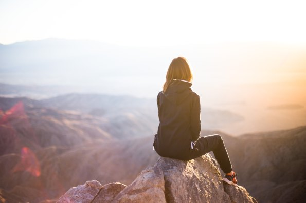 Woman sitting on top of grey rock overlooking mountain during daytime