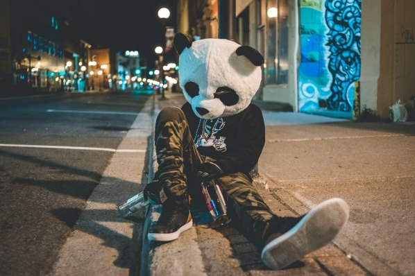 Person wearing costume panda head sits on the pavement with bottles of alcohol